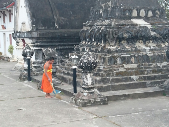 A monk sweeping outside one of the temples