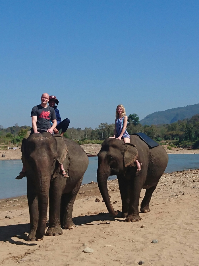 Couple ride elephants along the Nam Khan river in Laos