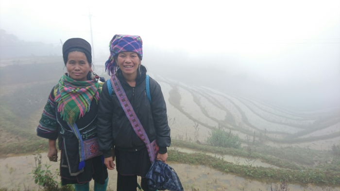 Two Hmong women standing on misty rice terraces outside Sapa in northern Vietnam