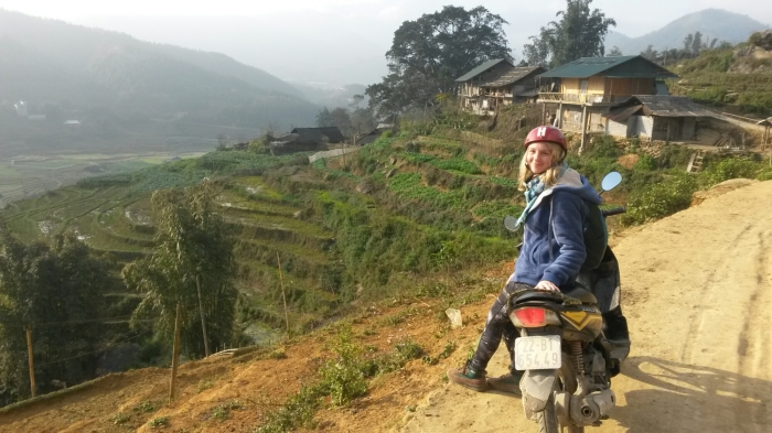 Girl sitting on motorbike on dusty track overlooking rice terraces in Vietnam