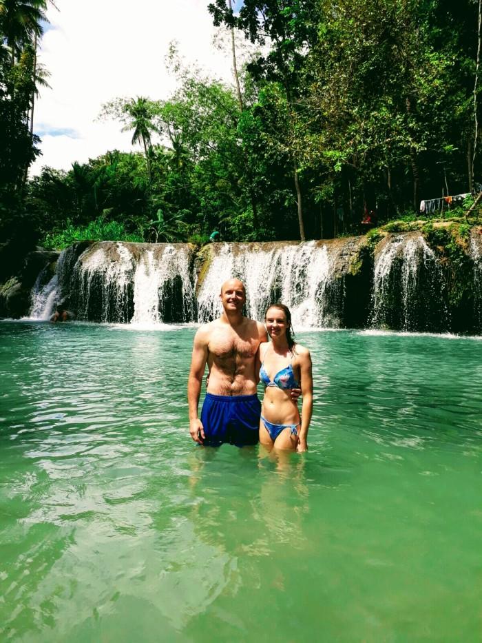 Couple standing beneath Cambugahay waterfall, Siquijor