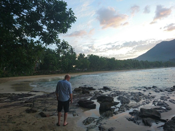 Man strolls along Sabang beach in Palawan at sunset