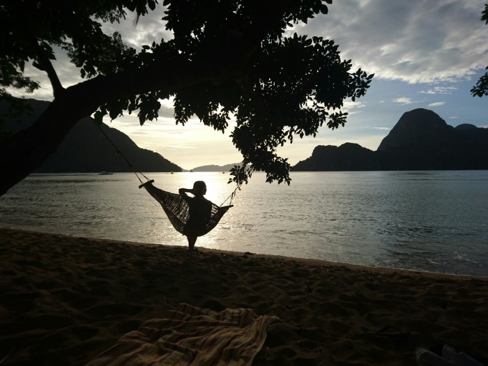 Hammock silhouetted against the sunset on Calaan beach, El Nido, Palawan, Philippines