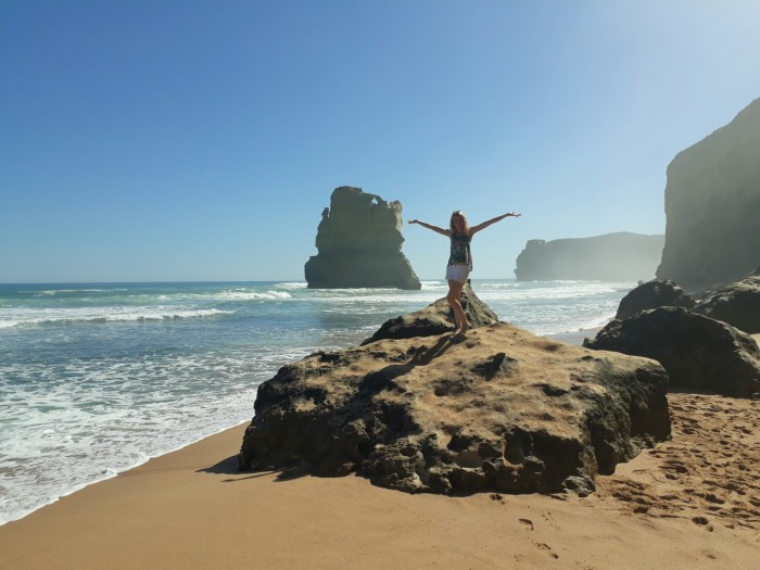Girl standing on a rock in front of the 12 Apostles on the Great Ocean Road