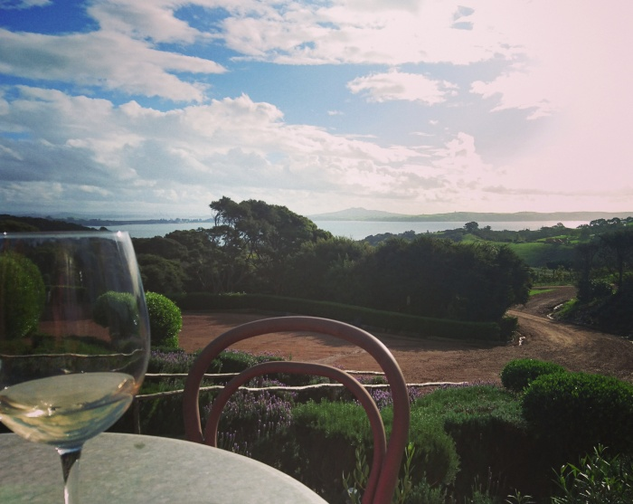 Wine glass on table overlooking Mudbrick Vineyard on Waiheke Island