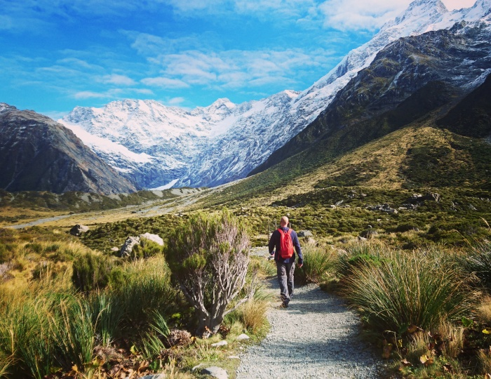 Walker strides through mountain scenery in Mt Cook National Park, New Zealand