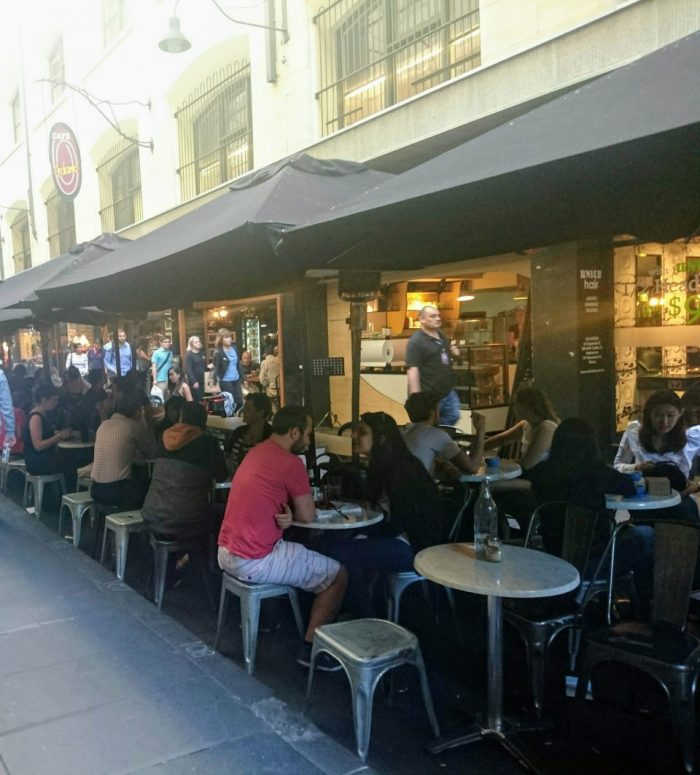 People sit at outdoor cafe in Melbourne