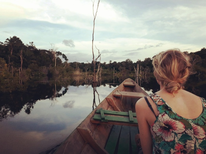 Girl travelling by boat down a river in the Amazon jungle