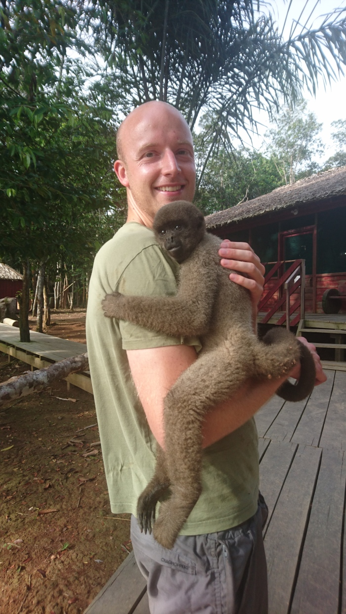 Man holds monkey in Amazon jungle