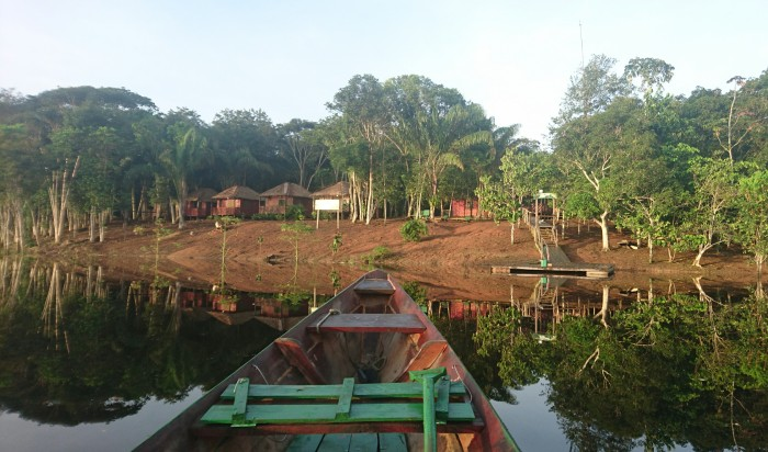 A boat approaching a remote jungle lodge in the Amazon