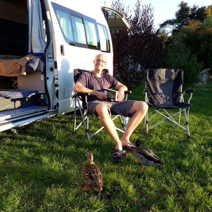 Man relaxing beside a campervan in New Zealand