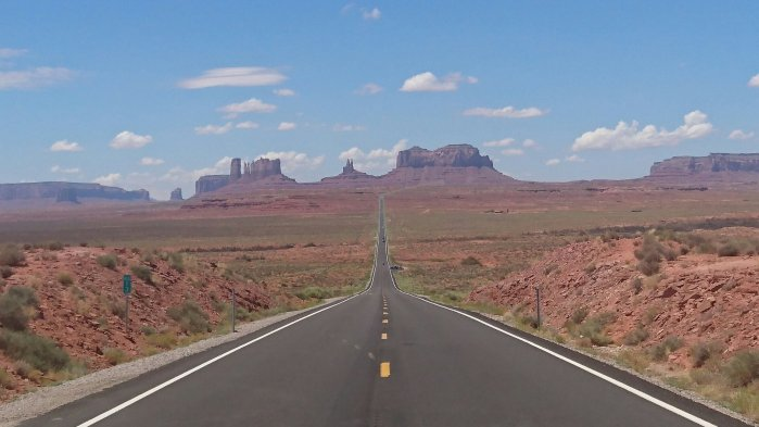 Long empty road stretching into the distance in Monument Valley, USA